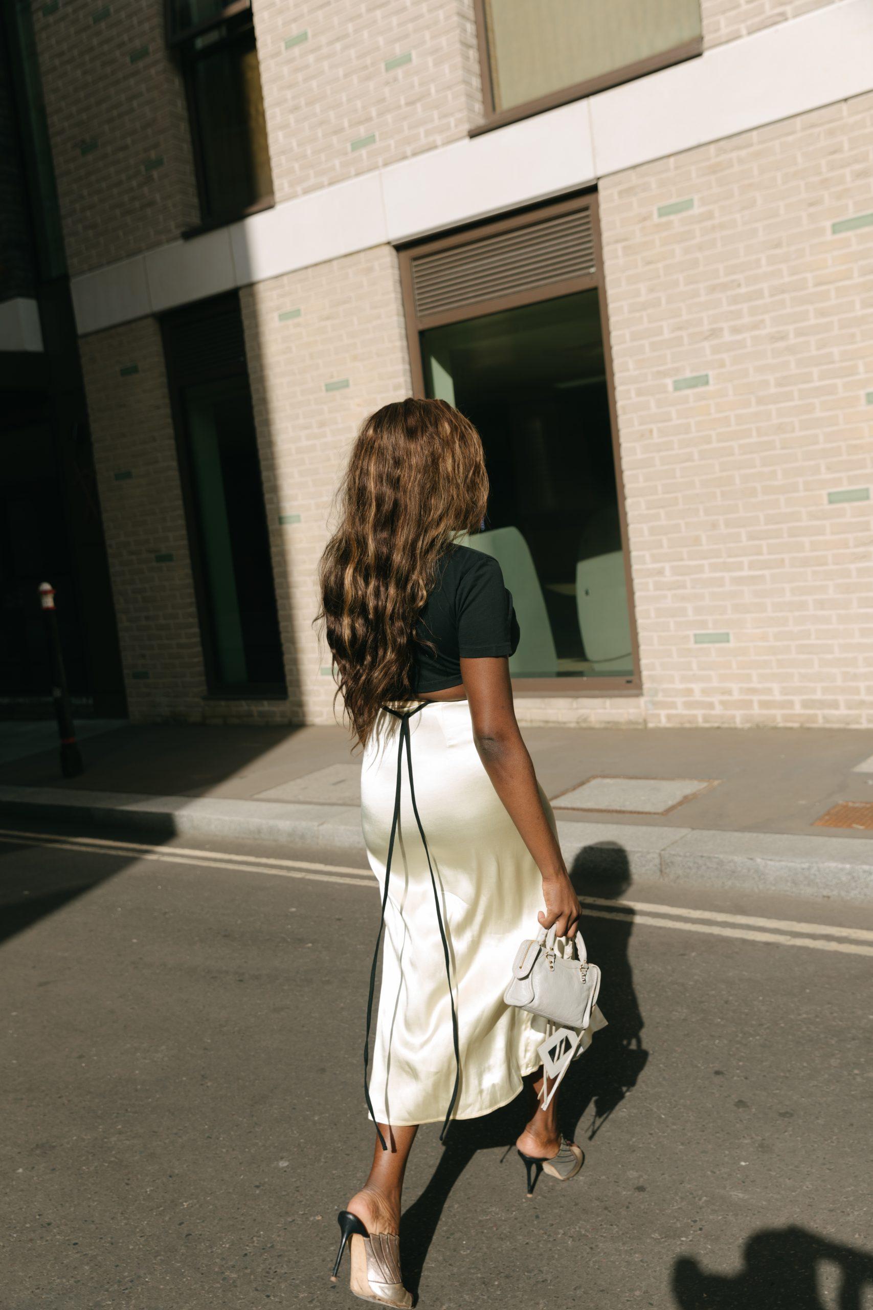 Jacquemus T-Shirt and Crop Top - Zara Satin midi skirt - Balenciaga mini city bag - back view walking -Tasha Antwi